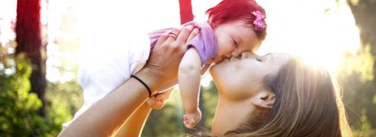 Foto di una donna che solleva e bacia una bambina.