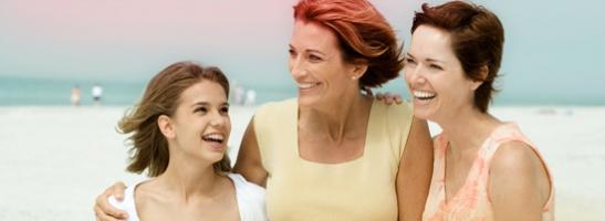 Foto di tre donne che si tengono vicine, una più giovane a sinistra e due più anziane a destra.