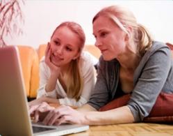 Foto di una madre e una figlia che usano assieme il computer. L'immagine illustra l'importanza della comunicazione e di aiutare tua figlia a trovare le informazioni giuste.