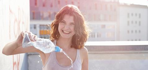 Foto di una giovane donna con in mano una bottiglietta da cui versa dell'acqua.